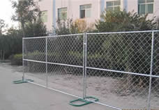 Two pieces of chain link portable fence panel with vertical and horizontal cross bars are fixed on the ground by two green metal feet.