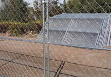 Two chain link portable fence panel with the horizontal cross bars are connected by the clamp and green feet.