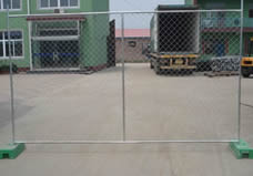 A piece of chain link portable fence panel with vertical cross bar is fixed on the ground by two green plastic feet.