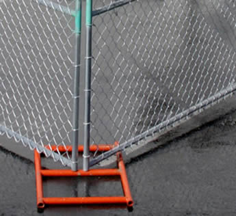 An orange powder coated metal fence feet are installed on the fence panels.