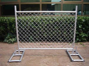 A chain link portable fence panel sample is on the ground with two metal feet.