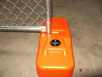 An orange plastic chain link portable fence feet is installed on the fence panel.