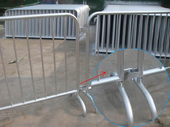 Two pieces of crowd control barriers are connected with the two same size bridge feet and a detail picture of the bridge feet .