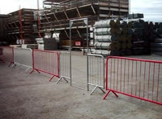 A piece of crowd control barrier gate is installed on the barriers in the construction site.
