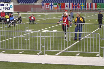 The crowd control barriers are installed on the stadium and several players on the grassland.