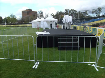 Crowd control barriers are installed on the grassland surrounding the stage.