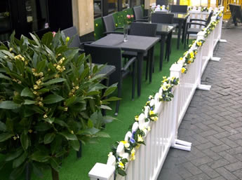 The picket event portable fences are installed in the open air coffee shop and several flowers on the portable fence.