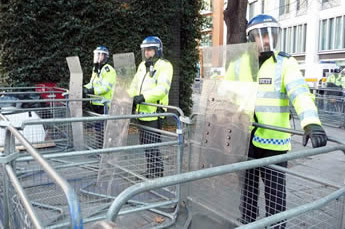 Police barriers form a strong barrier and three policeman stand behind of them.
