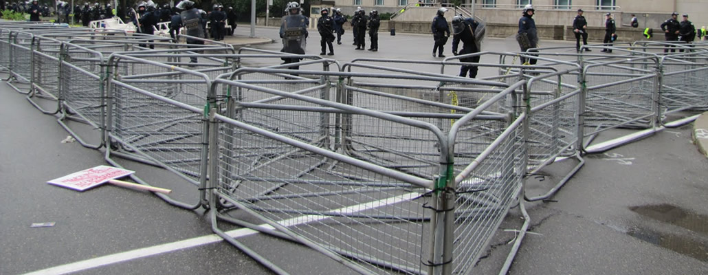 Police barriers are installed around an area and several policemen stand in the area.