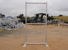 A piece of chain link portable fence gate is fixed by two metal feet.