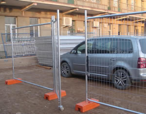A half-opened pedestrian gate and two welded portable fence panel, a car parked outside of the door.