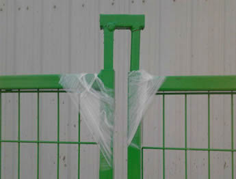 A green top coupler with round and square tubular legs are installed on the fence panel.