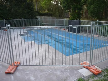 Portable pool fence are installed surrounding the swimming pool with the plastic base feet.