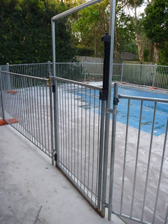 A portable pool fence gate and the fence panels is installed surrounding the pool.