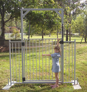 A piece of portable pool fence gate is installed on the grassland and a girl is holding the rail with her hand.