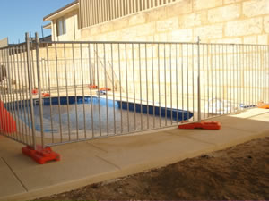 Portable fence panels are installed surrounding the swimming pool.