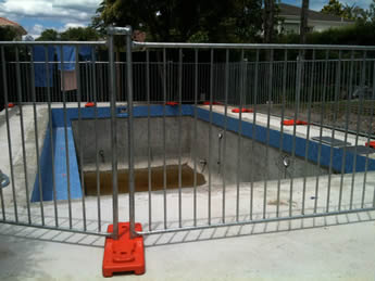 Portable pool fences are installed surrounding the renovating swimming pool.
