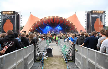 Two rows of stage barriers are installed on the front of the stage, many people at the behind of the barrier and many security personnel is working in the between of the barriers.
